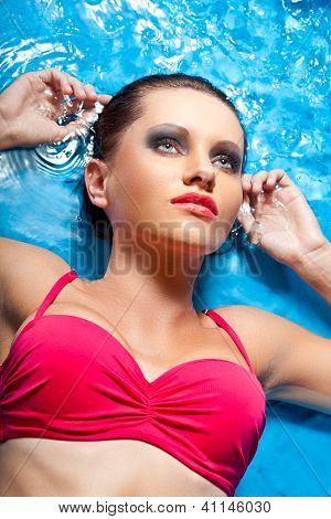 woman with smoky eyes laying in water