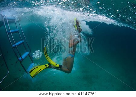 Underwater full length portrait of a young lady jumping into a tropical sea from a boat