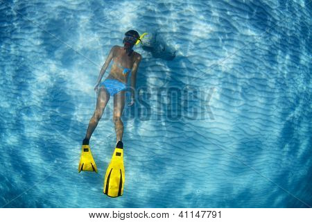 Young lady snorkeling in a transparent tropical sea over sandy bottom