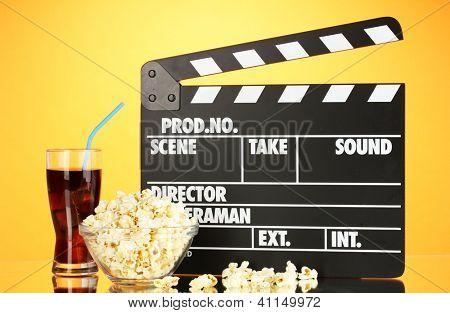 Movie clapperboard, cola and popcorn on orange background