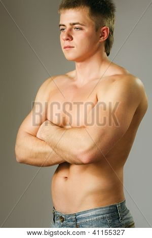 Strong man with a helathy body isolated over grey background