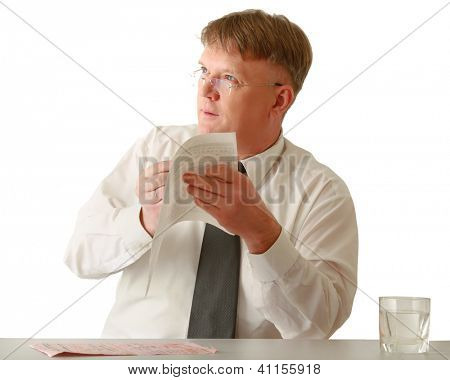 A businessman sitting on the desk and looking up, isolated on white background
