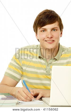 A young guy in front of a laptop studying, isolated on white
