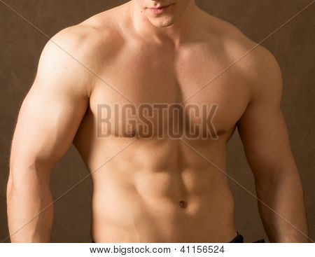 Strong man with a helathy body isolated over beige background