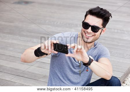 Attractive Male Model Taking Photos With A Black Smartphone