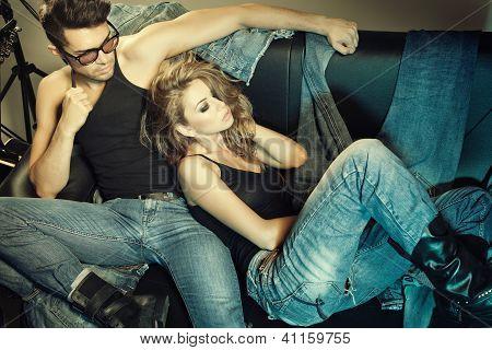 Homem sexy e mulher vestida de Jeans, fazendo uma sessão de fotos de moda em um estúdio profissional