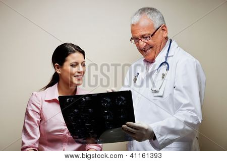 Senior male radiologist showing x-ray to female patient against colored background