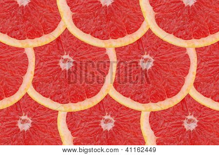 regular composition made of slices of red grapefruit