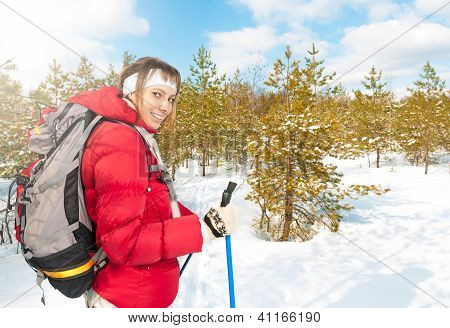 Young woman skiing in forest on winter sunny day.