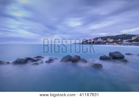 Dark Rocks In A Blue Ocean On Twilight. Castiglioncello, Italy