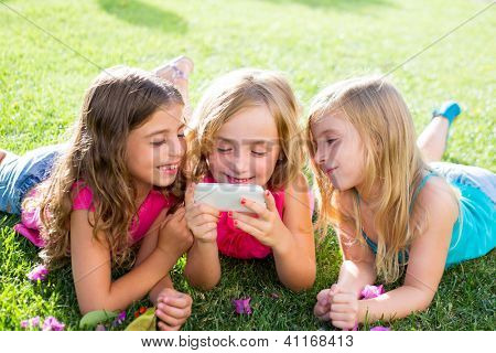 children friend girls group playing internet with mobile smartphone on grass