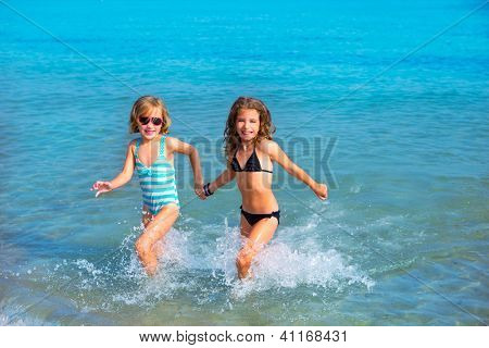 children girls friends running together in the beach shore on summer vacation