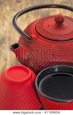 red hobnail tetsubin with a cup of tea - a detail of a traditional cast iron Japanese teapot set