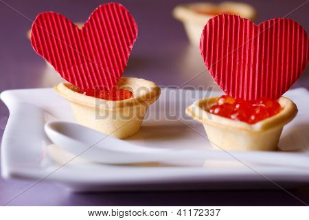 Tartlets with heart-shaped eggs on a glass base