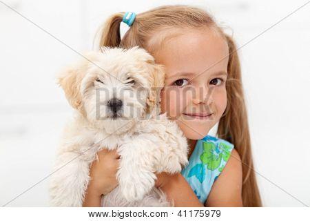 Little girl loves her fluffy dog posing together for the camera