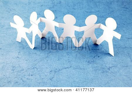 Group of six paper chain people holding hands together