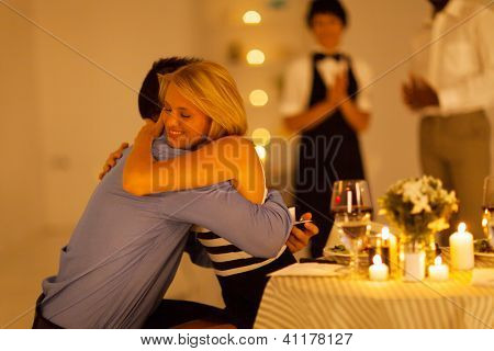 young woman hugging her boyfriend after he proposed in a restaurant