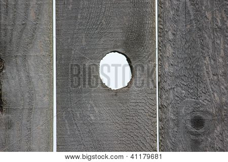 Open Knot Hole On Weathered Textured Wood Fence.