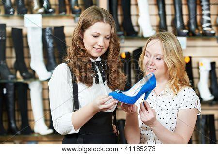 two Young woman choosing shoes during footwear shopping at shoe shop