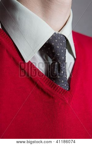 Man wearing white shirt with red sweater and necktie