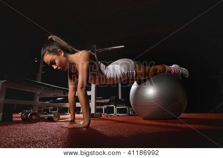 Woman exercising Pilates ball workout posture in fitness club