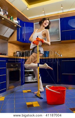Smiling young woman cleaning the floor at home and singing