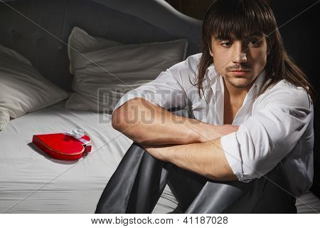 Portrait of man with heart shaped present on bed