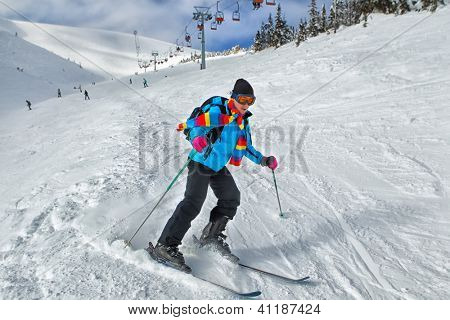 Young guy skier turning in powder snow; blue jacket; black pant