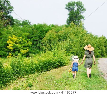 Happy Mother And Her Little Daughter Walking