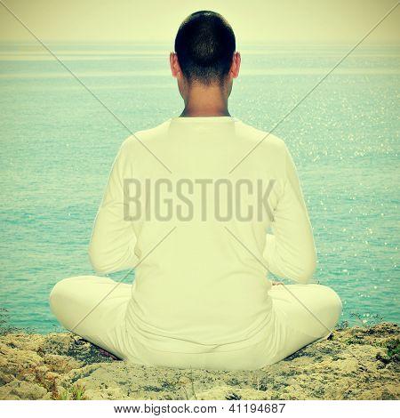 iemand mediteren tegenover de zee