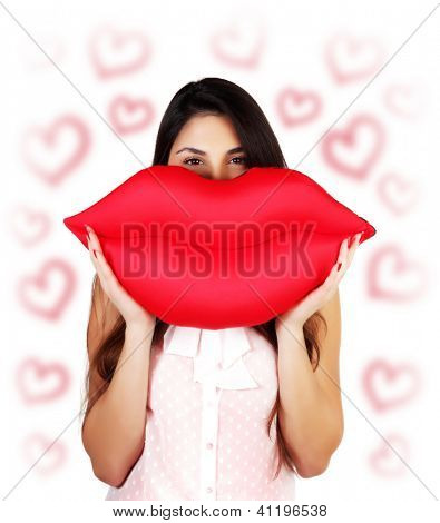 Photo of pretty brunette woman holding in hands big red lips, soft pillow-toy kiss-shaped, happy female having fun, isolated on white background with red heart shapes, Valentine day, love concept