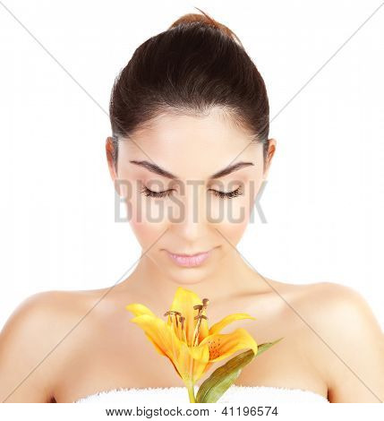 Photo of pretty woman enjoying dayspa, closeup portrait of attractive female with closed eyes holding yellow lily flower isolated on white background, luxury spa salon, beauty treatment concept