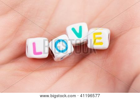 Photo of game cubes with love word on woman's palm, romantic holiday, affection symbol, romance relationship, colorful letters in the man's hand, Valentine day, happiness concept