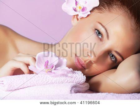 Picture of cute female with pink orchid flower in head lying down on massage table, healthy lifestyle, luxury spa resort, enjoying dayspa, aroma therapy, pampering and skin care concept
