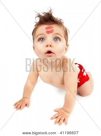 Image of funny baby boy crawling in studio, happy child with red kiss on the forehead isolated on white background, Valentine day, romantic holiday, adorable kid, love and care concept