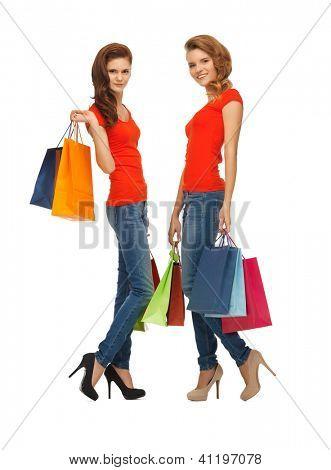 dois adolescentes em t-shirts vermelhas com sacos de compras