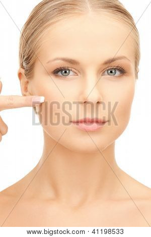 bright picture of beautiful woman pointing to cheek.