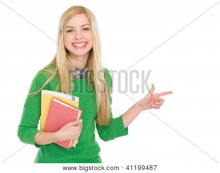 Smiling Student Girl With Books Pointing On Copy Space