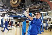 stock photo of suspension  - car mechanic with spanner tighten car suspension detail of lifted automobile at repair service station - JPG