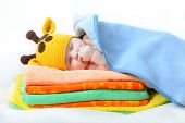 stock photo of sweet dreams  - cute sleeping baby boy in funny hand made giraffe hat - JPG
