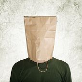 stock photo of embarrassing  - head in the paper bag man hidden behind theshopping bag - JPG