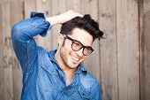 image of single man  - handsome young man smiling outdoors wearing glasses - JPG