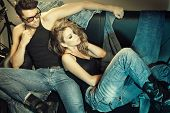 stock photo of casual wear  - Sexy man and woman dressed in jeans doing a fashion photo shoot in a professional studio - JPG