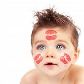 Image of lovely Cupid boy with red lipstick stamp on his cheeks and forehead isolated on white backg