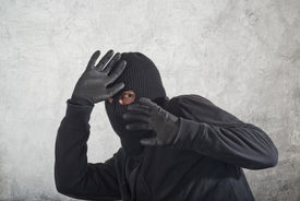 stock photo of shoplifting  - Catch the burglar concept thief with balaclava caught in front of the grunge concrete wall - JPG