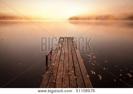 Small Wooden Pier On Still Lake In Autumnal Foggy Morning With Rising Sun