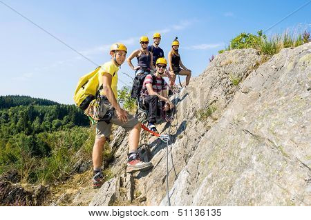 Group of climbers with safety equipment on rock