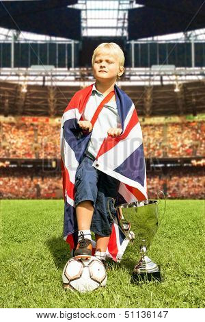Young boy, posing arrogantly with a British flag, a large trophy and a soccer ball in the center of a huge stadium