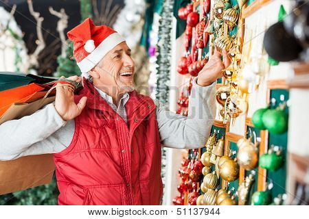 Happy senior man with shopping bags buying Christmas ornaments at store