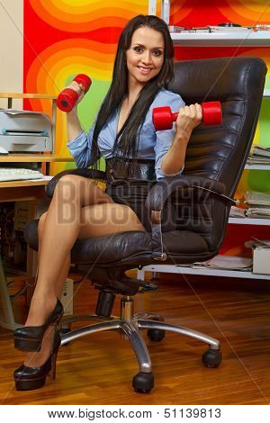 Office portrait of beautiful businesswoman stretching with dumbbells at her workplace